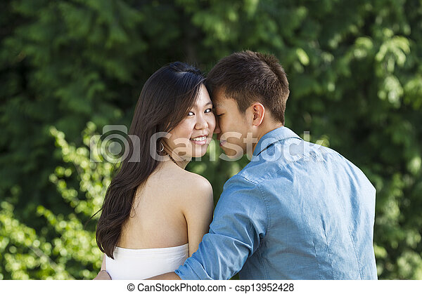 Young Adult Couple holding each other while outdoors  - csp13952428