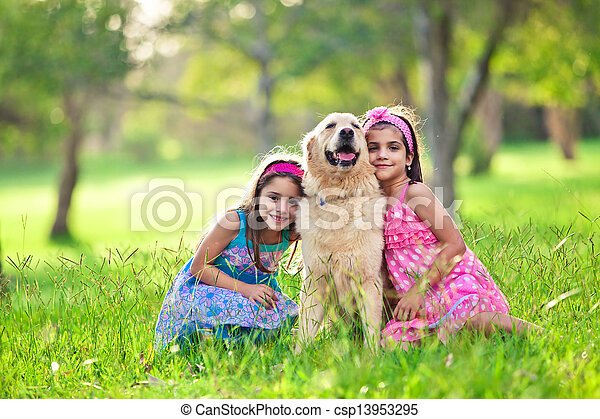 Two young girls hugging golden retriever in the park - csp13953295