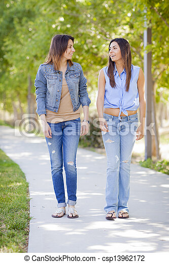 Young Adult Mixed Race Twin Sisters Walking Together - csp13962172