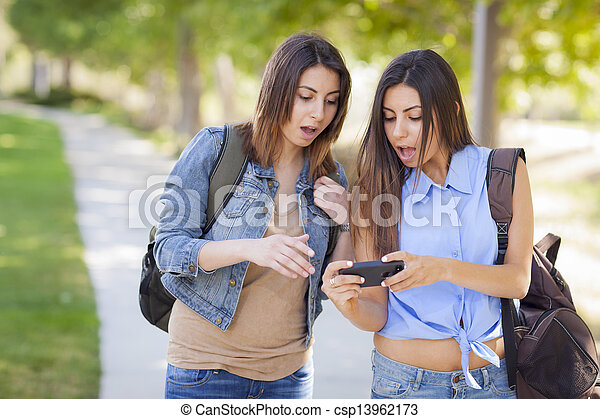 Young Adult Mixed Race Twin Sisters Sharing Cell Phone Experience Outside. - csp13962173