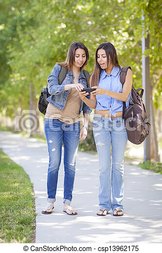 Young Adult Mixed Race Twin Sisters Sharing Cell Phone Experience Outside. - csp13962175