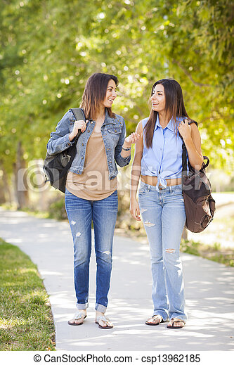 Young Adult Mixed Race Twin Sisters Walking Together - csp13962185