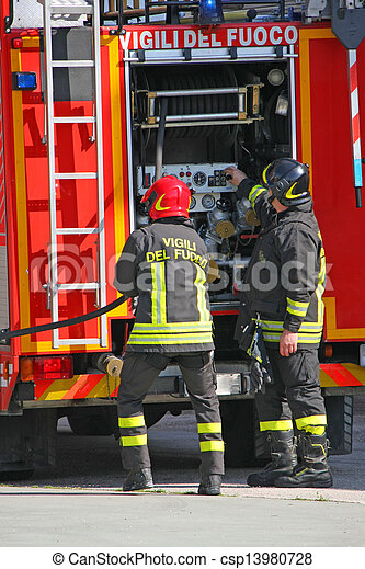 firefighters in action during a fire with the fire truck and the water hose