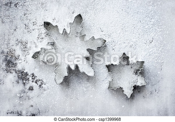 Snowflake cookie cutters on a powdered baking sheet - csp1399968