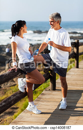 middle aged couple drinking water after exercising - csp14008187