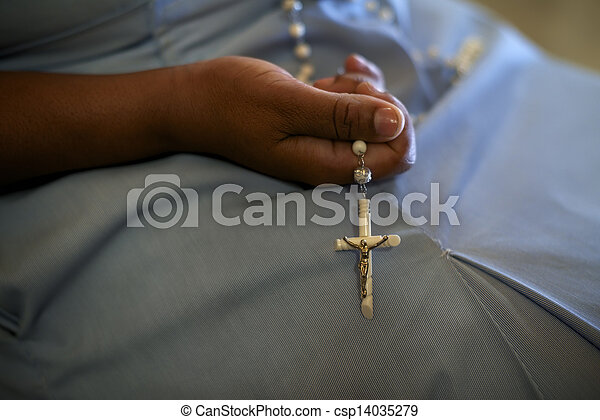 People and religion, catholic sister praying in church and holding cross in hands. With model release - csp14035279