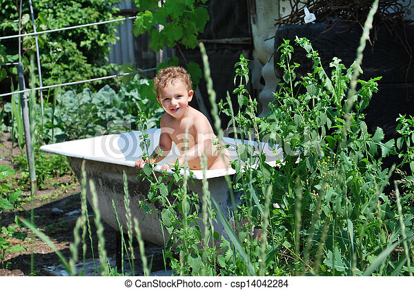 In the summer, in rural areas, outdoors, little boy bathes in the bath, indulge in, splashing water - csp14042284