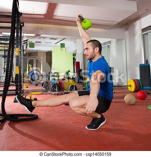 Crossfit fitness man balance Kettlebells with one leg - csp14050159