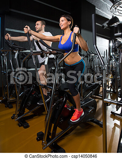elliptical walker trainer man and woman at black gym - csp14050846