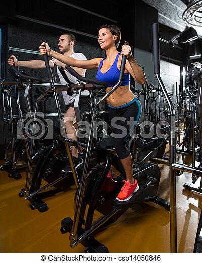 elliptical walker trainer man and woman at black gym - csp14050846
