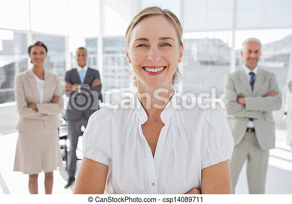 Cheerful businesswoman standing with arms folded - csp14089711