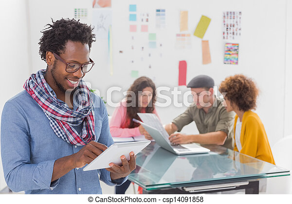 Smiling man using tablet with creative team working behind