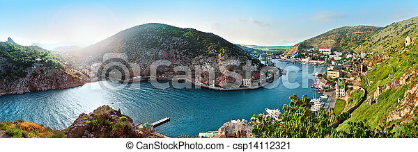 sea bay landscape with blue sky mountains and green grass - csp14112321