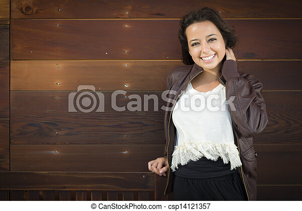Mixed Race Young Adult Woman Portrait Against Wooden Wall - csp14121357