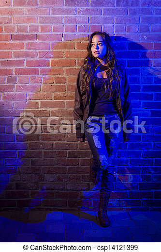 Pretty Mixed Race Young Adult Woman Against a Brick Wall - csp14121399
