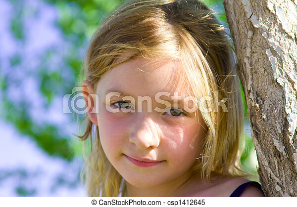 Stock Photo - 6 year old girl smiling leaning against a tree in the ...