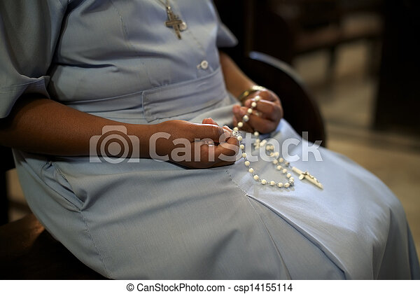 People and religion, catholic sister praying in church and holding cross in hands. With model release - csp14155114