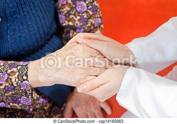 Young sweet doctor holds the old woman\'s hand