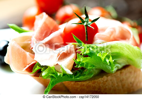 Sandwiches with prosciutto on plate macro - csp14172050
