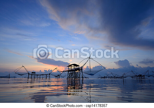 silhouette traditional fishing method using a bamboo square dip net with sunrise background in Patthalung, Thailand - csp14178357