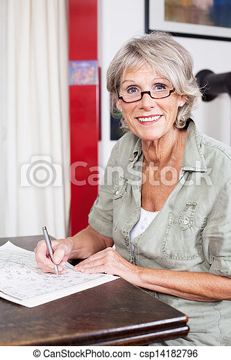 Senior woman completing a crossword puzzle - csp14182796