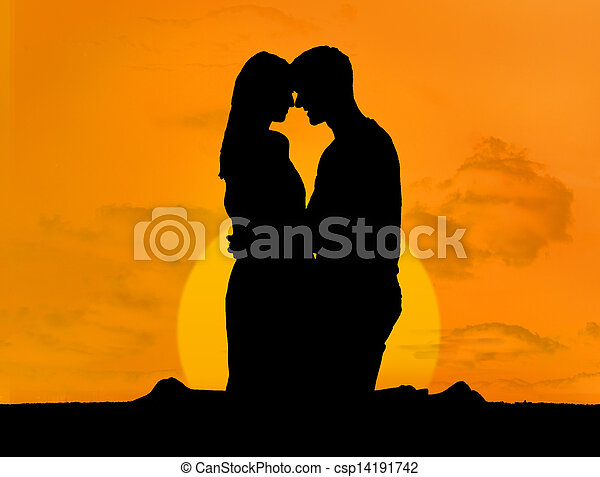 Silhouette of couple embracing under a sunset - csp14191742