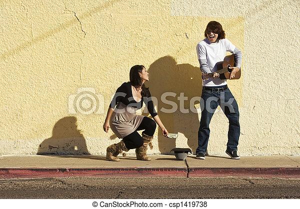 Musician on Sidewalk and Woman Pedestrian - csp1419738