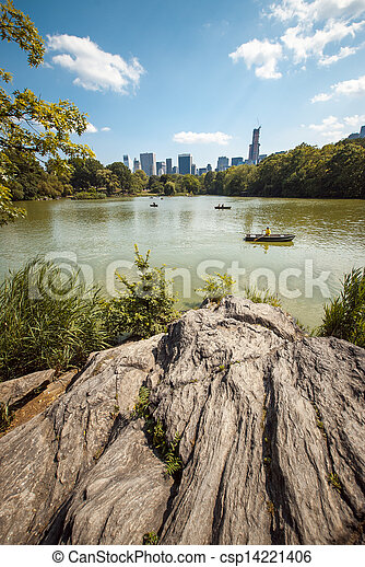 A view of a lake in Central Park, New York City, on a summer day, with people enjoying it. On the foreground, rocks can be seen, and on the background, buildings and skyscrapers. - csp14221406