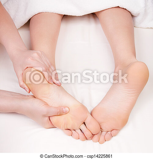 Therapist doing feet massage, pressing reflexology zones on the woman's foot - csp14225861