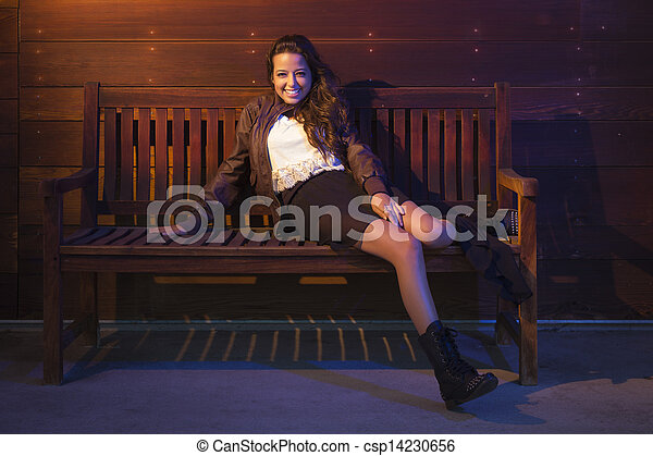 Mixed Race Young Adult Woman Portrait Sitting on Wood Bench - csp14230656