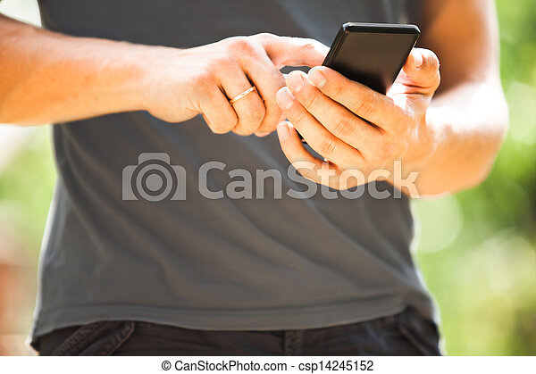 Man using mobile smart phone outdoor in summer - csp14245152