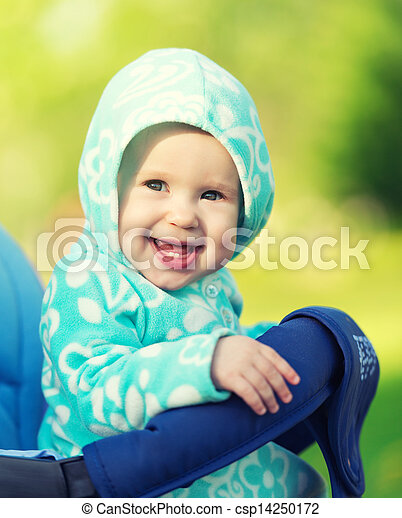 happy little baby girl smiling in a blue hood in the stroller for a walk in the nature park - csp14250172