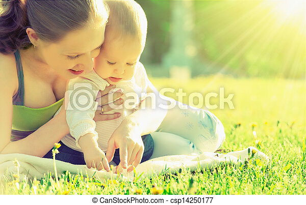 happy family. Mom and baby resting in a meadow in the summer outdoors in the park - csp14250177