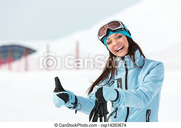 Half-length portrait of woman who goes skiing and wears goggles and sports jacket for winter sports