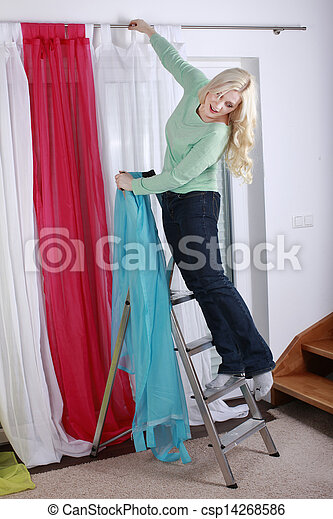 woman hanging up curtains - csp14268586