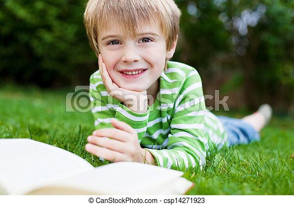 smiling Boy Reading book in the garden