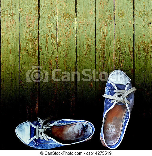 worn jeans gym shoes against a wooden plank wall - csp14275519