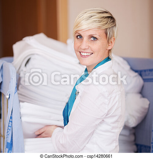 Housekeeper Stacking Sheets In Stock Room