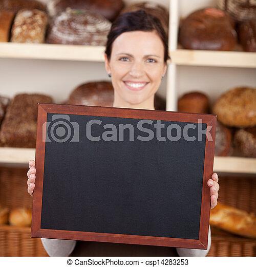 Bakery worker holding a blank chalkboard