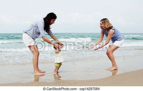 two beautiful girls with a baby on the beach - csp14297084