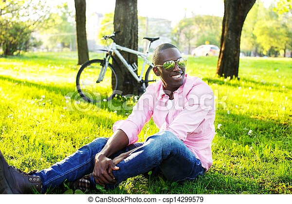 Young happy smiling african american wearing sunglasses with bicycle behind him in a park - csp14299579
