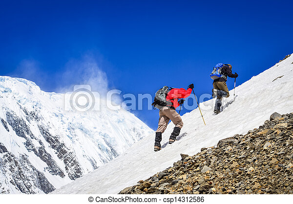 Two mountain trekkers on snow with peaks background - csp14312586