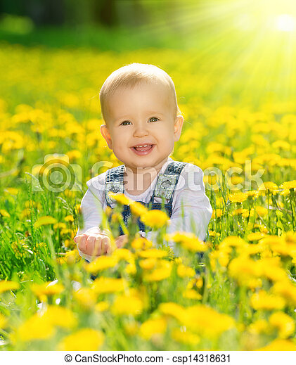 happy baby girl on  meadow with yellow flowers  on the nature - csp14318631