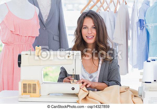 Smiling fashion designer using sewing machine - csp14327859