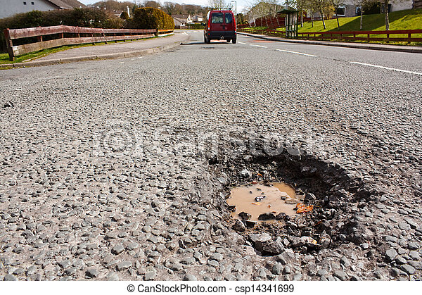 Pot hole in residential road surface - csp14341699