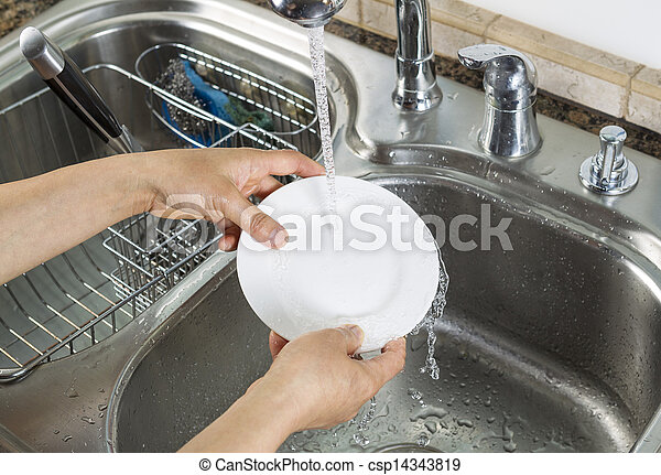 Woman hands washing dinner plate in kitchen sink - csp14343819