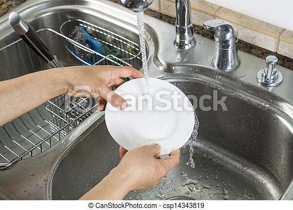 Woman hands washing dinner plate in kitchen sink  - csp14343819