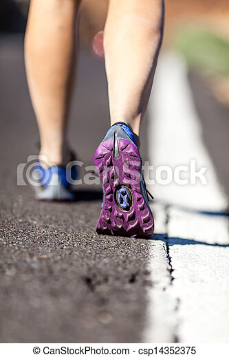 Walking or running legs on asphalt road, adventure and exercising in summer nature.Female hiker or runner foot and sport shoes doing workout outdoors. - csp14352375