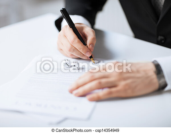 man hands with gambling dices signing contract - csp14354949