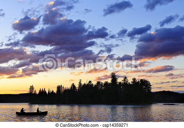Canoe on lake at sunset - csp14359271